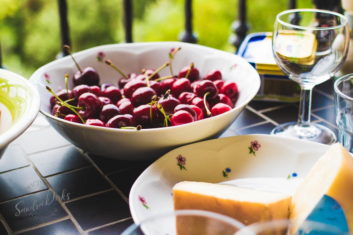 Sandra Dirks - Tisch mit Abendessen auf dem Balkon Kirschen